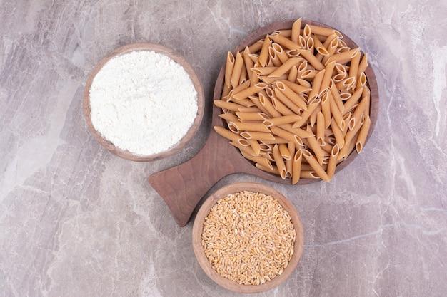 カップに小麦粉と小麦粉をブレンドした木製の大皿にパスタ