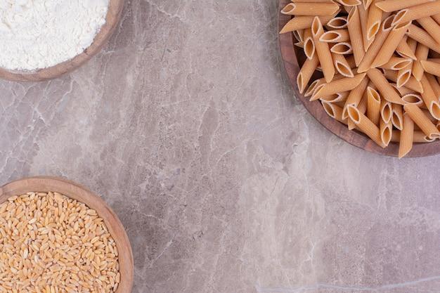 Паста на деревянном блюде с пшеницей и мукой в деревянных чашках.