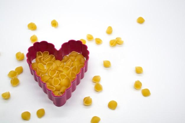 Макароны на белом фоне с формочкой для печенья в форме сердца
