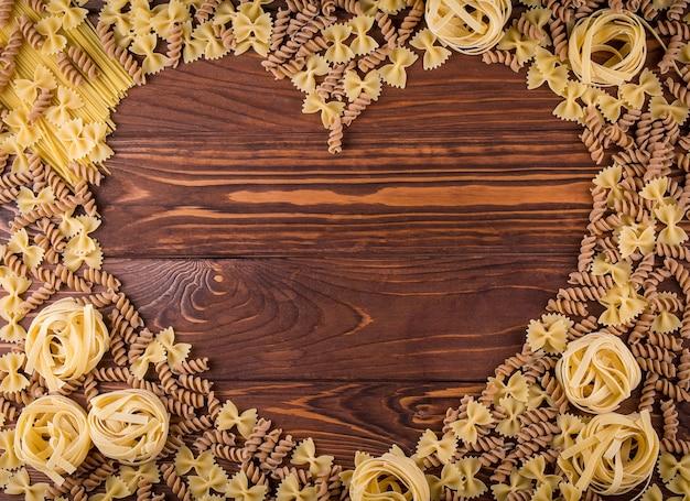 Макаронные изделия на деревянных фоне. вид сверху с копией пространства. ингредиенты для хлебобулочных изделий.