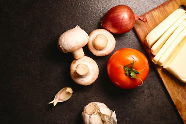 요리를위한 파스타 또는 피자 재료. 평면도. 이탈리아 음식 개념. 토마토, 버섯, 치즈, 양파, 향신료. 공간 복사