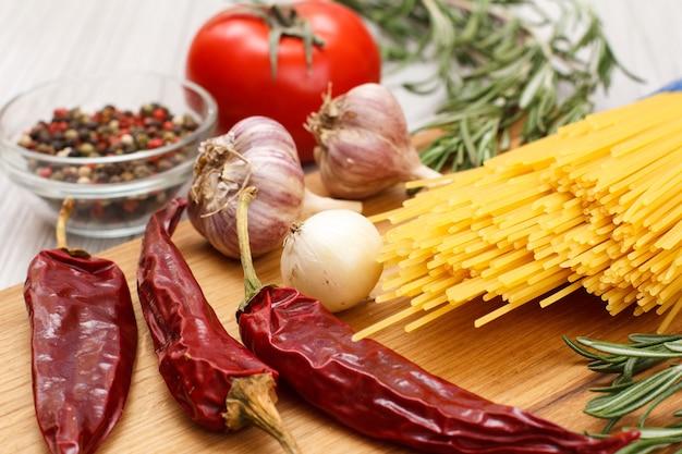 木製のまな板で肉や魚を調理するための材料を使ったパスタやスパゲッティ。にんにく、ガラスのボウルにピーマン、唐辛子、トマト、タマネギ、ローズマリーを机の上に。