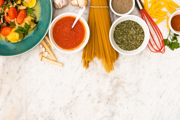 Pasta and pasta ingredients on marble textured backdrop