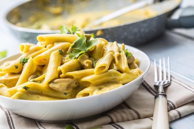 Паста пене с кусочками курицы, грибами, пармезаном, сырным соусом и украшением из зелени