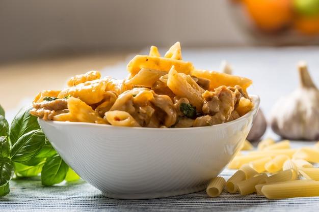 Паста пенне с куриными кусочками, грибами, базиликом и сыром пармезан, итальянская еда в белом шаре на кухонном столе.