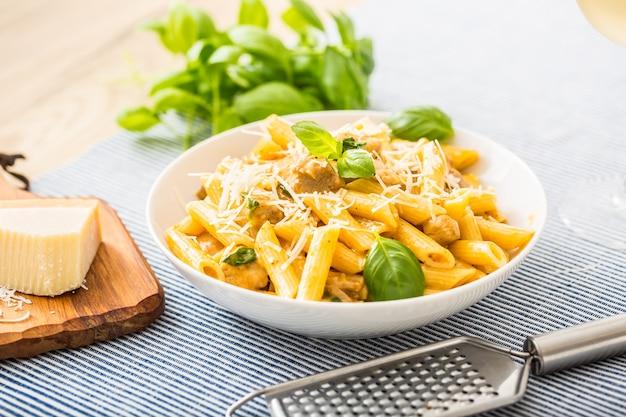 Паста пенне с кусочками курицы, грибами, базиликом, пармезаном и белым вином. итальянская еда в белой тарелке на кухонном столе.