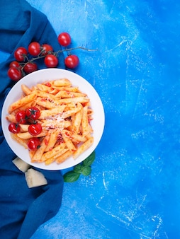 Pasta penne with tomato sauce, fresh basil, roasted tomatoes and parmesan