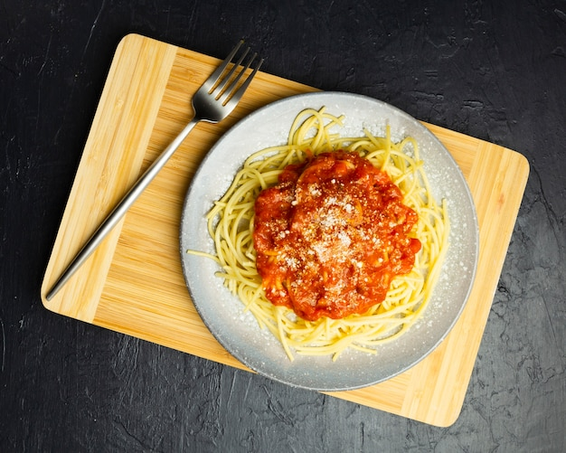 Pasta plate on chopping board with fork