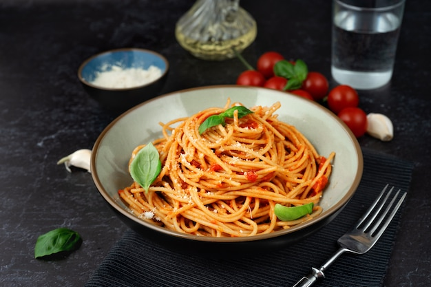 Pasta in a plate with tomato sauce on black background