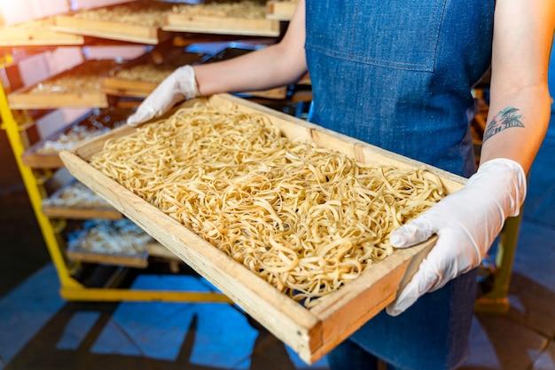工場でのパスタ生産。マカロニ休憩用の木箱。技術生産工場の産業作業、生のマカロニのクローズアップ。