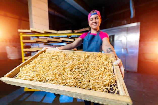 工場でのパスタ生産。パン屋の手に麺が入った木箱。技術生産工場の産業作業、生のマカロニのクローズアップ。