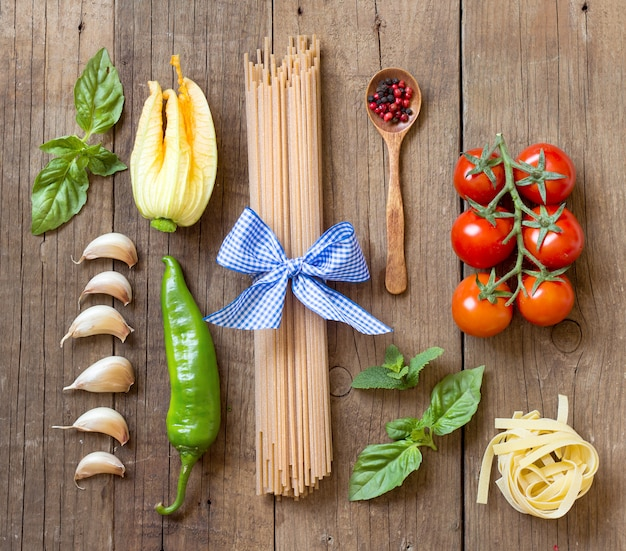 Pasta and raw vegetables on wooden background top view with copy space