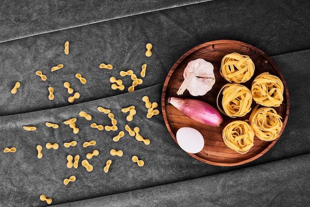 パスタは野菜と一緒に木製の大皿に巻かれます。