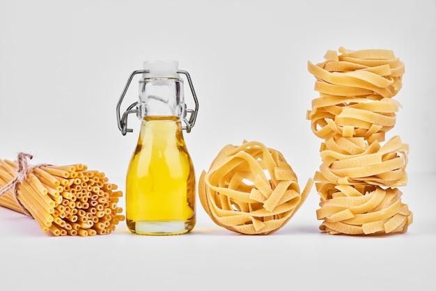 Rotoli di pasta con una bottiglia di olio.
