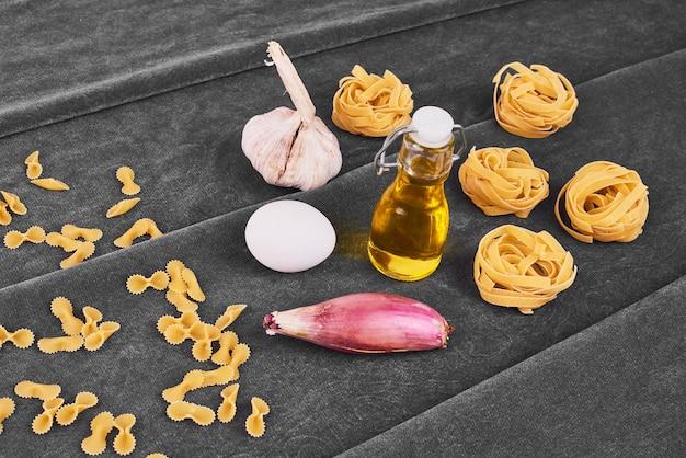 Rotoli di pasta con ingredienti sul nero.