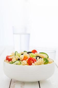 흰색 나무 테이블에 야채와 함께 그릇에 파스타 샐러드
