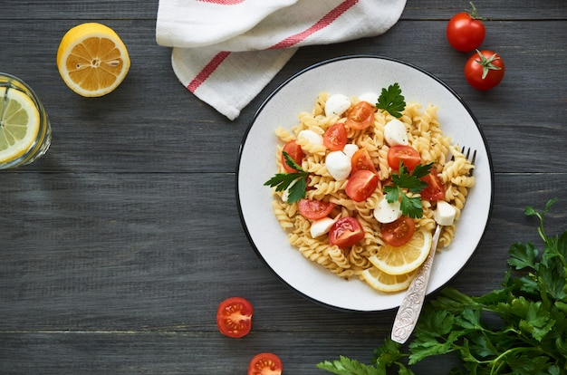 Pasta salad with cherry tomatoes and mozzarella on a plate