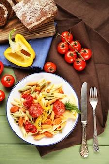 고추, 당근, 토마토 나무 테이블에 파스타 샐러드