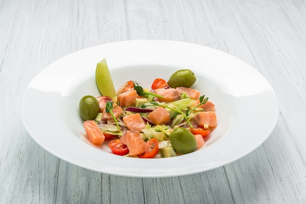 Pasta salad with smoked salmon, olives, cherry tomatoes, pink pepper and fresh basil home made food symbolic image