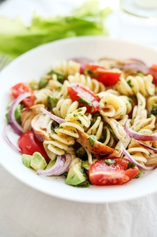 Салат из пасты с помидорами, авокадо, курицей и красным луком