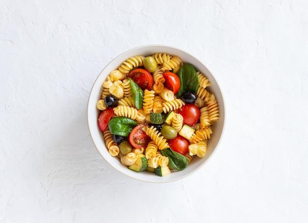 토마토, 호박, 올리브, 시금치와 파스타 샐러드. 건강한 식생활. 채식주의 자 음식.