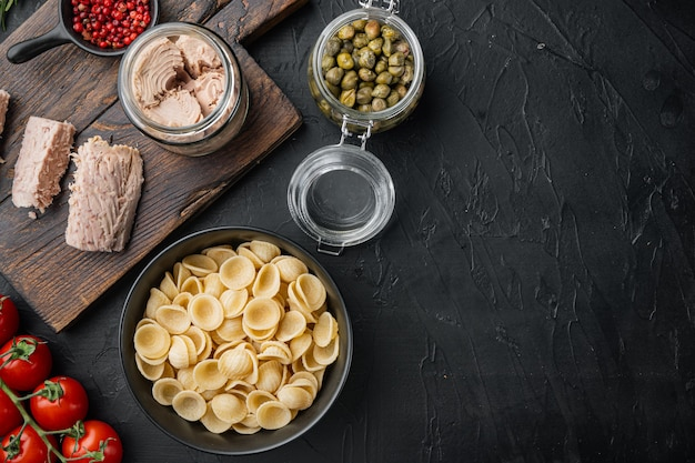 Салат из пасты с ингредиентами из тунца на черном, плоская планировка