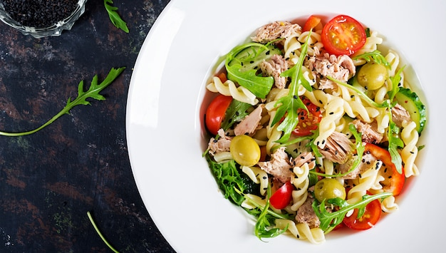 Pasta salad with tuna, tomatoes, olives, cucumber, sweet pepper and arugula on rustic background