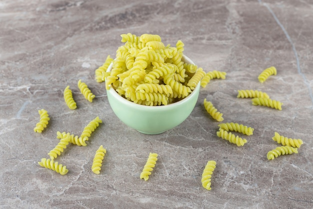 Pasta scattered from a full bowl , on the marble surface.