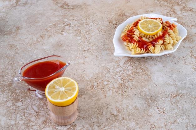 Pasta che serve con fette di limone e un bicchiere di ketchup sulla superficie in marmo
