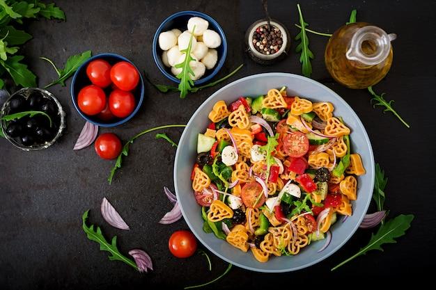 Insalata di pasta a forma di cuore con pomodori, cetrioli, olive, mozzarella e cipolla rossa alla greca. disteso. vista dall'alto