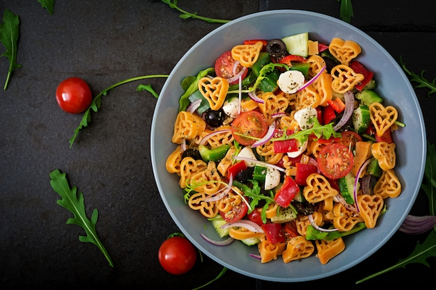 Pasta in the shape heart salad with tomatoes, cucumbers, olives, mozzarella and red onion greek style. flat lay. top view