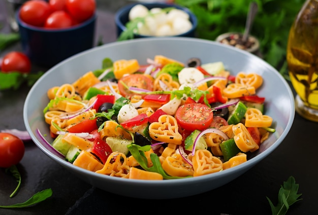 Pasta in the shape heart salad with tomatoes, cucumbers, olives, mozzarella and red onion greek style.