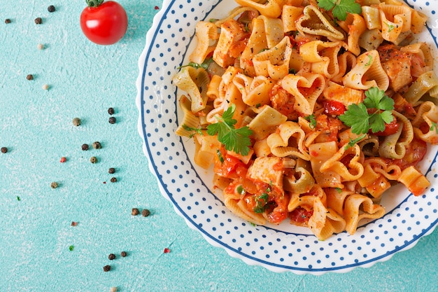 Pasta in the shape of hearts with chicken and tomatoes in tomato sauce. top view