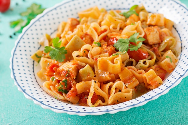 Pasta in the shape of hearts with chicken and tomatoes in tomato sauce.