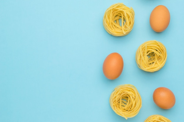 Pasta in the shape of nests and eggs on a blue background. space for your text. ingredients for making pasta.