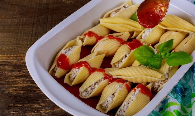Pasta shells stuffed with beef, ricotta cheese with tomato sauce.