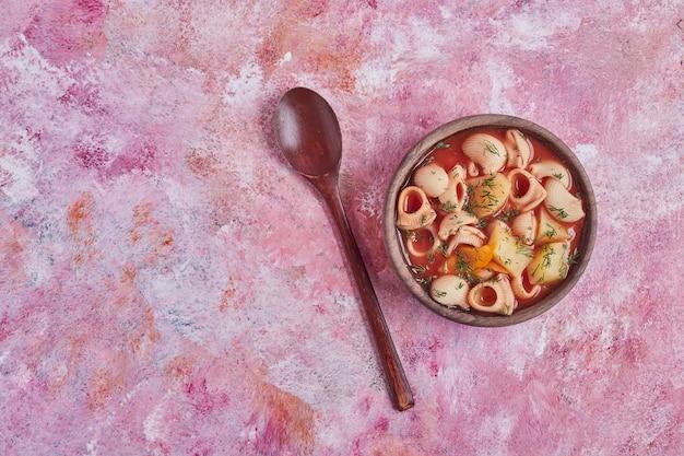 Zuppa di pasta in salsa di pomodoro in una tazza di legno.