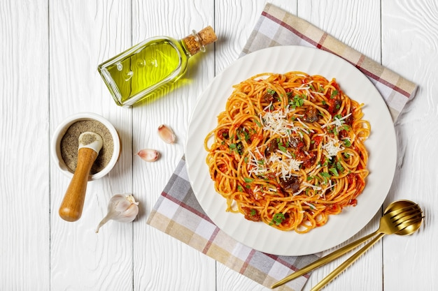 Pasta spaghetti alla norma on a white plate on a white textured wooden table with ingredients, italian cuisine, horizontal view from above, flat lay