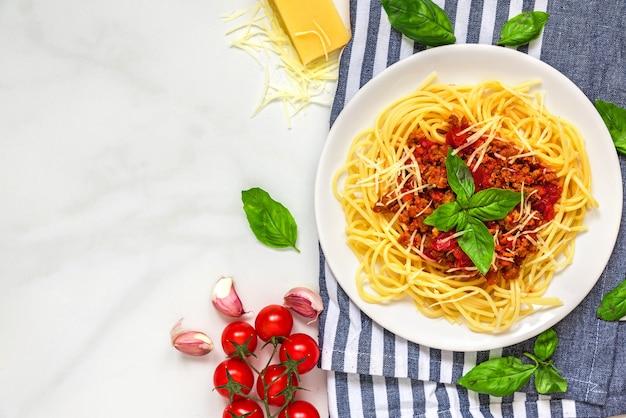 白い大理石のテーブルの上のキッチンタオルの上の白い皿にパスタスパゲッティボロネーゼ。健康食品。上面図