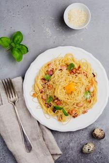 Паста спагетти карбонара с беконом, сыром пармезан, яичным желтком и листьями базилика на серой светлой поверхности. традиционное итальянское блюдо