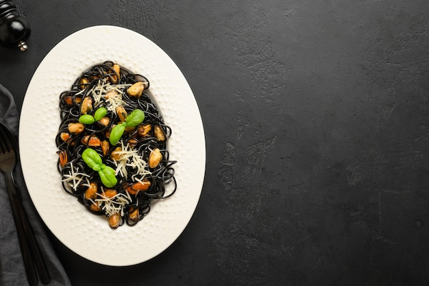 Pasta spaghetti squid ink with mussels in white plate on black.