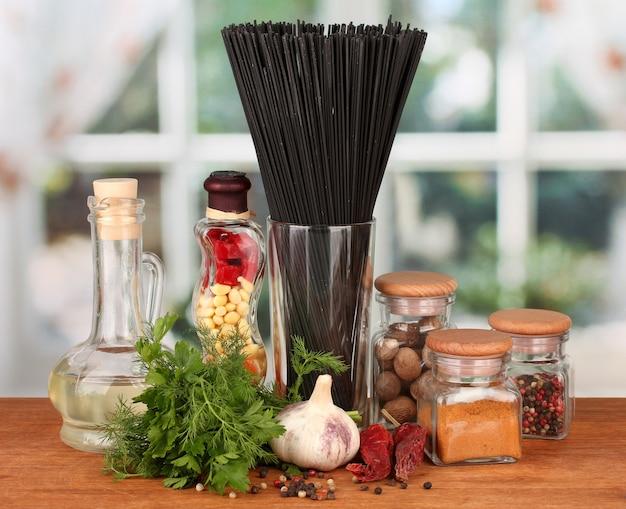 Паста спагетти, овощи и специи на деревянном столе на ярком фоне