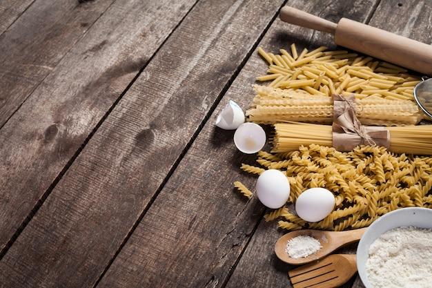 Pasta spaghetti with flour, egg on old wood
