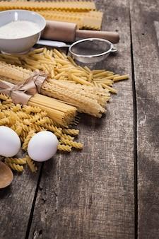 小麦粉、古い木製の背景に卵とパスタスパゲッティ