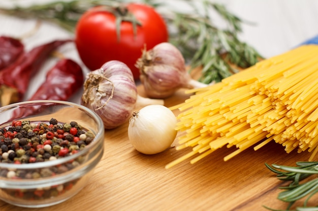 Pasta or spaghetti with ingredients for cooking meat or fish on a wooden cutting board. garlic, allspice peppers in glass bowl, chili pepper, tomato, onion and rosemary on the background.