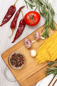 Pasta or spaghetti with ingredients for cooking meat or fish on a wooden cutting board. garlic, allspice peppers in glass bowl, chili pepper, tomato, onion and rosemary. top view.