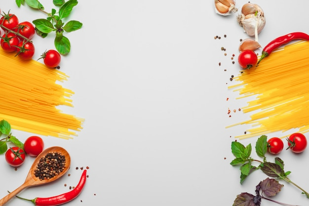 Pasta spaghetti with ingredients for cooking pasta on a white background, top view.
