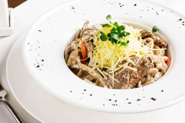 Pasta spaghetti with meat, cheese and herbs in white plate