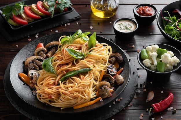 Макаронные изделия спагетти с грибами и овощами на черной тарелке. концепция меню.