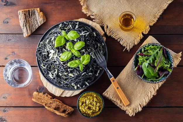 파마산 치즈, 바질, 페스토 소스를 곁들인 파스타 스파게티. 나무 판자에 검은색 파스타, 소스 페스토, 채소의 신선한 믹스 샐러드. 플랫 레이. 평면도